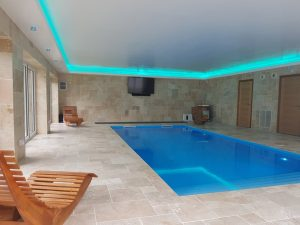 Pool-house LED strip lighting creates an aquamarine hue