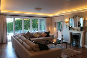Living area with picture window and coving LEDs