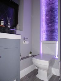 Bare brick feature wall in ensuite bathroom lit by LEDs - view 1