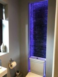 Bare brick feature wall in ensuite bathroom lit by LEDs - view 2